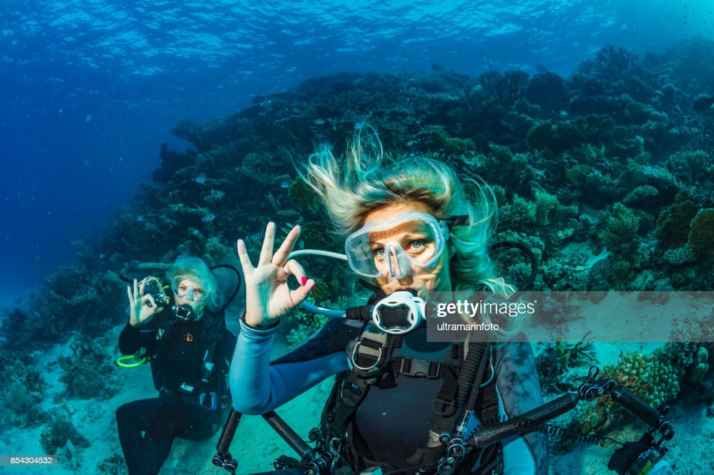 Scuba diver is exploring and enjoying Coral reef  Sea life Couple Two sporting women Underwater photographer : Stock Photo