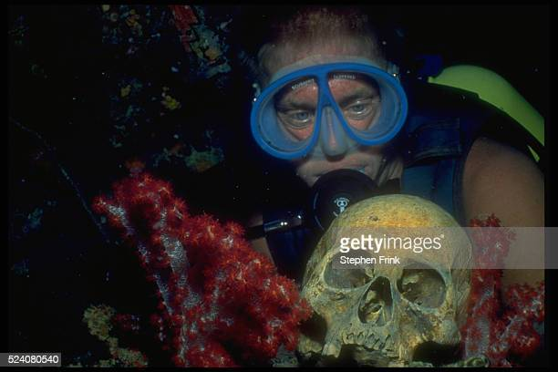 A scuba diver looks at a human skull in Truk Lagoon the site of a major sea battle of World War II The reminders of the battle are a major attraction...