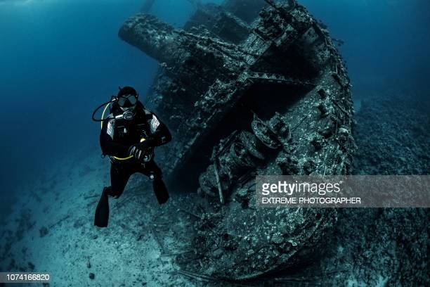 scuba diver maintaining his depth underwater next to a giant rusted shipwreck in the red sea - sunken stock pictures, royalty-free photos & images