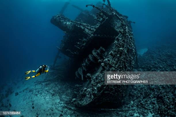 scuba diver observing a large shipwreck completely rusted and overgrown lying underwater in the red sea - sunken stock pictures, royalty-free photos & images