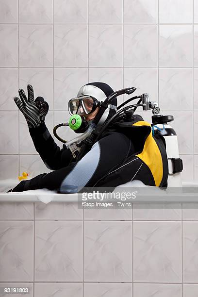 a scuba diver sitting in a bubble bath giving the ok sign - out of context stock pictures, royalty-free photos & images