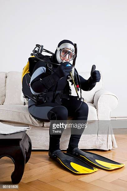 A scuba diver sitting on a couch in a living room giving a thumbs up sign