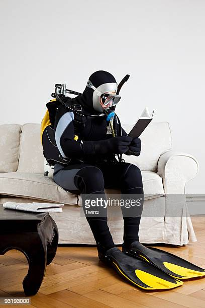 A scuba diver sitting on a couch reading a book
