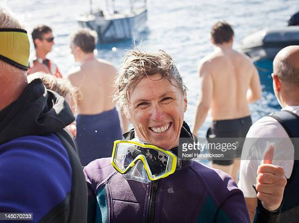 A scuba diver smiles right after her ocean dive