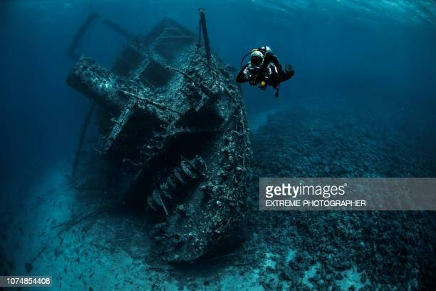 scuba diver swimming away from a large overgrown shipwreck in the red sea - sunken stock pictures, royalty-free photos & images