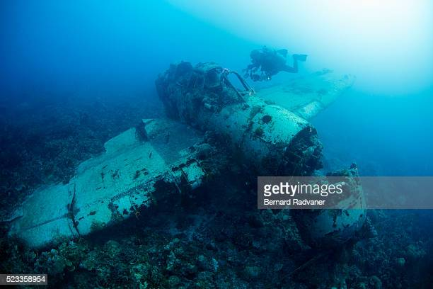 scuba diver swimming near wreck of japanese fighter plane, palau - sunken stock pictures, royalty-free photos & images