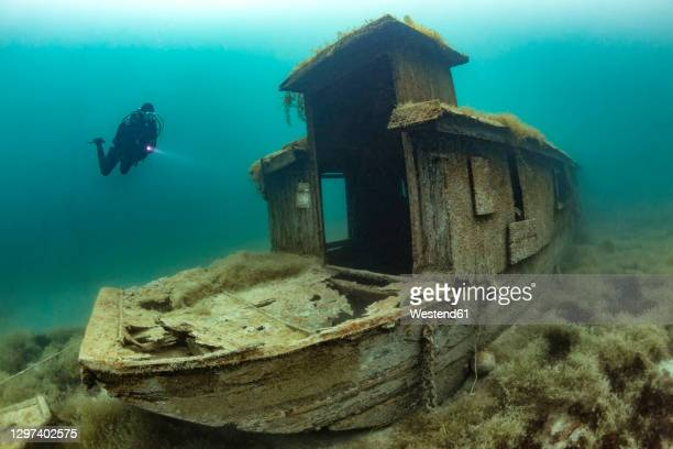 scuba diver swimming toward shipwreck sunken in lake atter - sunken stock pictures, royalty-free photos & images