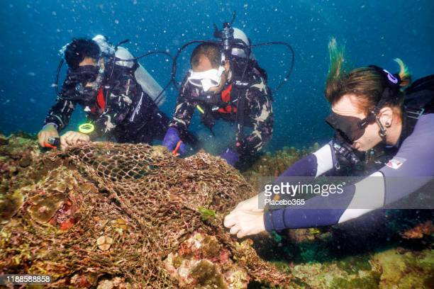 scuba diver volunteers on underwater environmental cleanup of ghost net fishing gear - aqualung diving equipment stock pictures, royalty-free photos & images