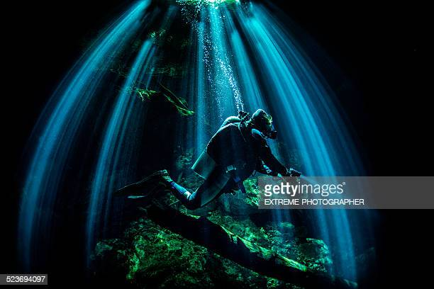 Scuba diver with flashlight in the cave