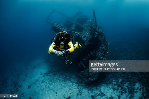 scuba diver with yellow suit diving away from the shipwreck underwater in the red sea - sunken stock pictures, royalty-free photos & images