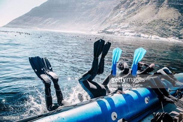 Scuba Divers Diving From Boat In Sea