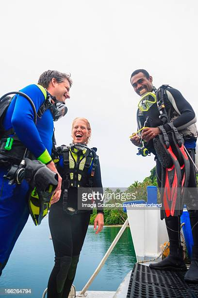 Scuba divers laughing on boat