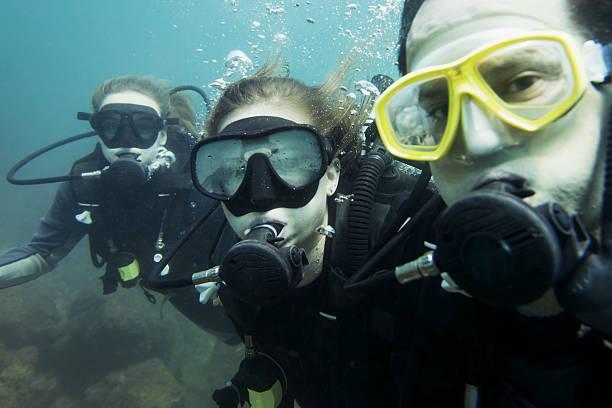 Scuba divers posing underwater; Ixtapa-Zihuatanejo, Guerrero, Mexico