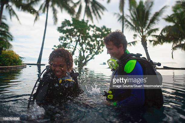 Scuba divers splashing in water