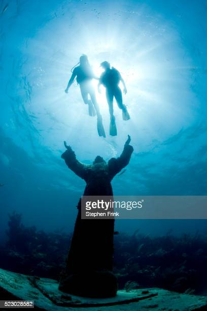 Scuba Divers Swimming Above Christ of the Deep Statue