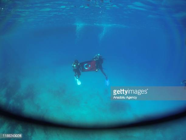 Scuba divers unfurl a Turkish flag underwater in Kas district of Turkey's southern Antalya province on July 03 2019 Antalya's Kas district is...