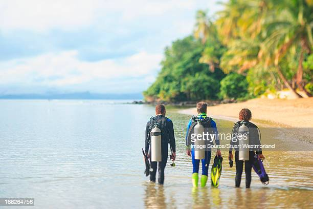 Scuba divers walking on tropical beach