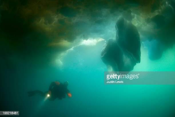 Scuba diving below icebergs with flashlight
