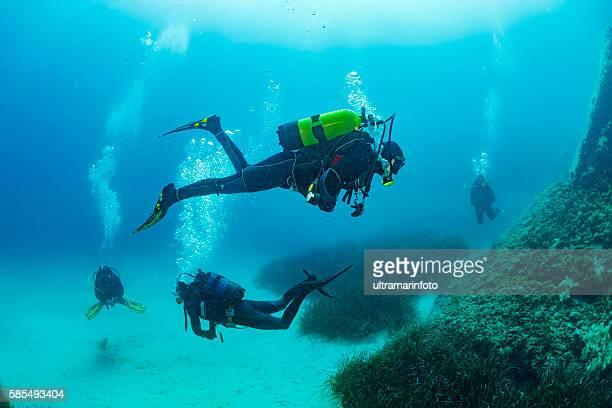 scuba diving    underwater group of scuba divers in blue - sporttauchen stock-fotos und bilder