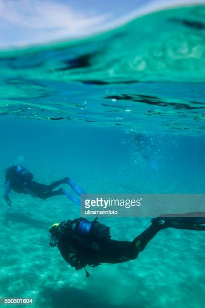 scuba diving    underwater two scuba diver in blue lagoon - aqualung diving equipment stock pictures, royalty-free photos & images