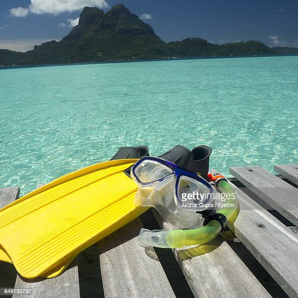 Scuba Mask With Diving Flippers On Pier Over Sea