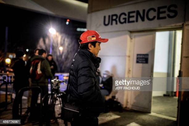 A Scuderia Ferrari and Michael Schumacher fan waits on December 29 2013 in Grenoble in front of the emergency department of the Centre Hospitalier...