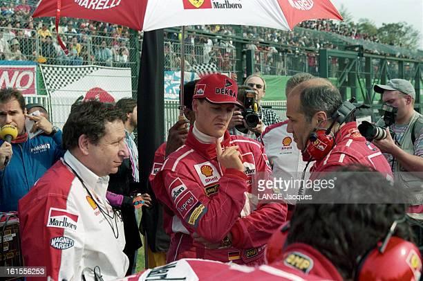 Scuderia Ferrari At The Grand Prix Of Japan 1998 Jean TODT et Michael SCHUMACHER en combinaison de pilote de course sous un parasol publicitaire sur...