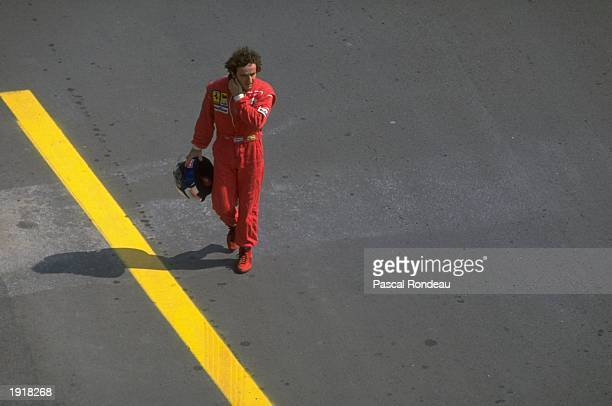 Scuderia Ferrari driver Alain Prost of France walks back to the pits during the Hungarian Grand Prix at the Hungaroring circuit in Budapest Hungary...