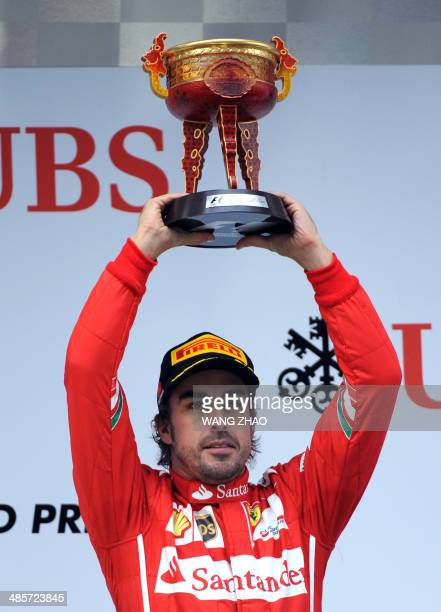 Scuderia Ferrari driver Fernando Alonso of Spain lifts his trophy after winning third place in the Formula One Chinese Grand Prix in Shanghai on...