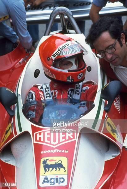Scuderia Ferrari driver Niki Lauda of Austria and Mauro Forghiere chat before a race Mandatory Credit Allsport UK /Allsport