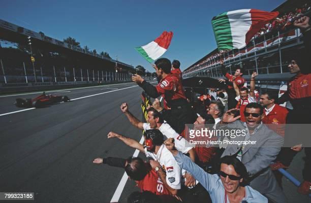 Scuderia Ferrari team members salute Michael Schumacher from the pit lane wall as he takes the chequered flag driving the Scuderia Ferrari Ferrari...