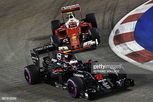 Scuderia Ferrari's Finnish driver Kimi Raikkonen chases McLaren Honda's British driver Jenson Button during the qualifying session in Singapore on...