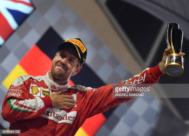Scuderia Ferrari's German driver Sebastian Vettel celebrates after taking the third place at the end of the Abu Dhabi Formula One Grand Prix at the...