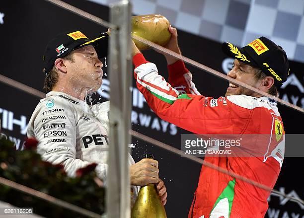 Scuderia Ferrari's German driver Sebastian Vettel sprays sparkling wine on Mercedes AMG Petronas F1 Team's German driver Nico Rosberg as they...