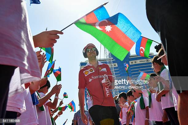 Scuderia Ferrari's German driver Sebastian Vettel walks to a truck for the parade tour at the Baku City Circuit on June 19 2016 in Baku ahead of the...