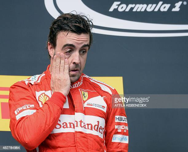 Scuderia Ferrari's Spanish driver Fernando Alonso reacts on the podium after the Hungarian Formula One Grand Prix at the Hungaroring circuit in...