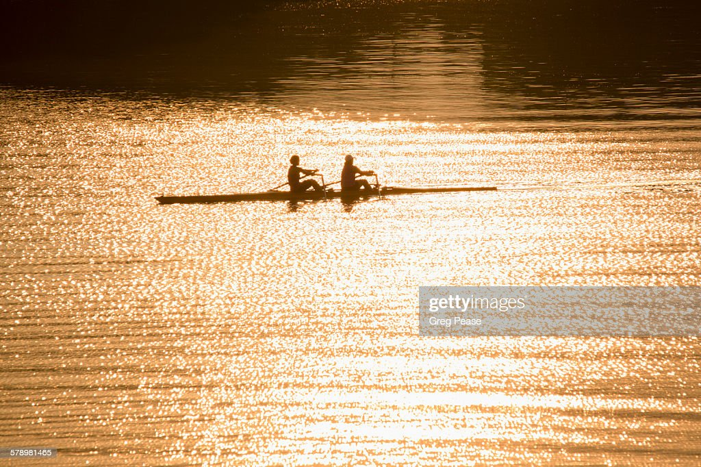 Sculling during sunrise practice : Stock Photo