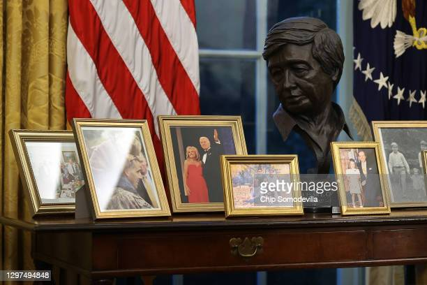 Sculpted bust of Cesar Chavez is seen with a collection of framed photos on a table as U.S. President Joe Biden prepares to sign a series of...