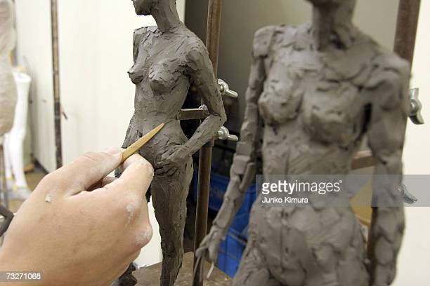 A sculptor adjusts the modelling clay on a mannequin at the studio of Japan's leading mannequin maker Yoshichu Mannequin Co on February 9 2007 in...