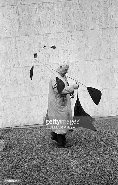 Sculptor Alexander Calder Makes A Mobile For The Palace Of Unesco A Paris devant le palais de l'UNESCO Alexandre CALDER en imperméable tenant une...