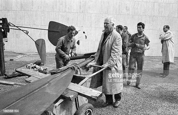 Sculptor Alexander Calder Makes A Mobile For The Palace Of Unesco A Paris devant le palais de l'UNESCO Alexandre CALDER en imperméable une cigarette...