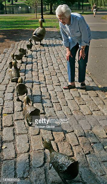 """Sculptor and artist Nancy Schon from West Newton looks over and wipes down her """"Make Way For Ducklings"""" sculpture, which will be turning 20 years..."""