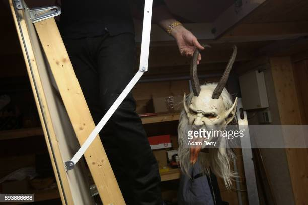 Sculptor and woodworker Rupert Kreuzer brings a Krampus mask down from the attic in his workshop on December 15 2017 in Grossarl near Salzburg...