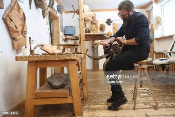 Sculptor and woodworker Rupert Kreuzer carves a Krampus mask in his workshop on December 15 2017 in Grossarl near Salzburg Austria Krampus is a...