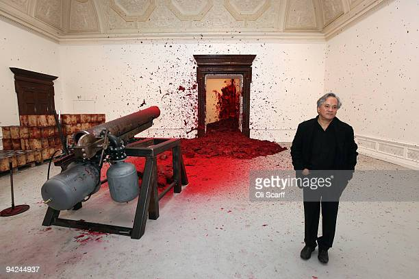 Sculptor Anish Kapoor poses for photographs in front of his artwork 'Shooting into the Corner' in the Royal Academy of Arts on December 10 2009 in...