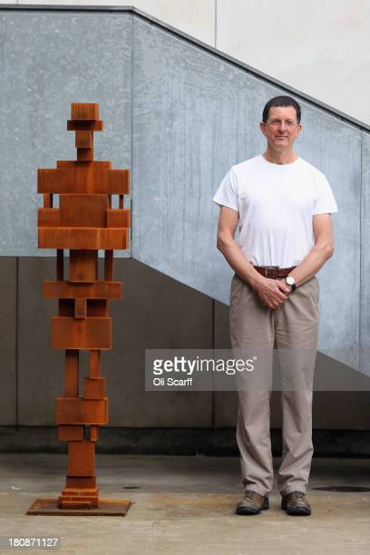 Sculptor Anthony Gormley stands next to his work at his studio following the announcement that he has been awarded the Sculpture Laureate in the...