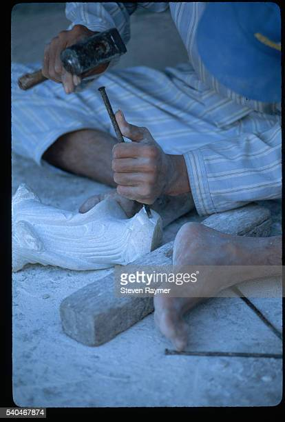 A sculptor carves a piece of marble at Thuy Son Mountain the most sacred of the five Marble Mountains at Da Nang Vietnam