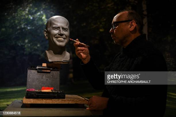 Sculptor Claus Velte puts the finishing touches to the head of a wax statue of US President elect Joe Biden before its installation at the Grevin wax...