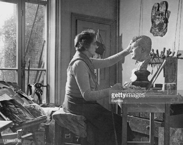 Sculptor Jane Jackson works on a clay head of politician John F. Kennedy, ready to be displayed at Madame Tussauds in London, 30th November 1960.