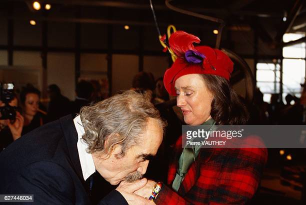 Sculptor Jean Tinguely kisses the hand of fellow artist Niki de SaintPhalle while at the Musee National d' Art Moderne in Paris The two are attending...